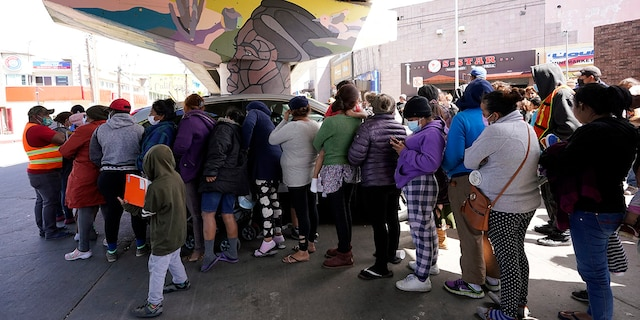 People surround a car as it arrives carrying food donations at a makeshift camp for migrants seeking asylum in the United States at the border crossing Friday, March 12, 2021, in Tijuana, Mexico. (AP Photo/Gregory Bull)