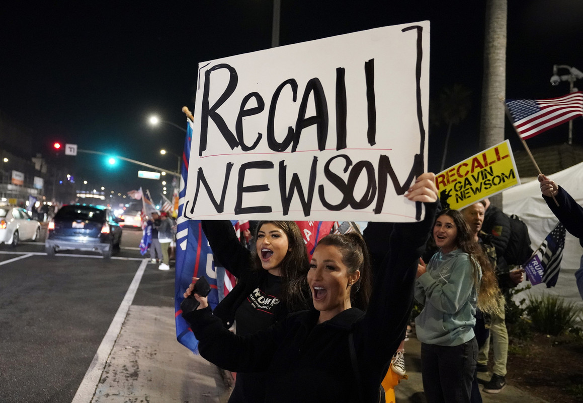 Trump supporters shout slogans while carrying a sign calling for a recall on California Gov. Gavin Newsom during a protest against a stay-at-home order amid the COVID-19 pandemic in Huntington Beach, Calif.